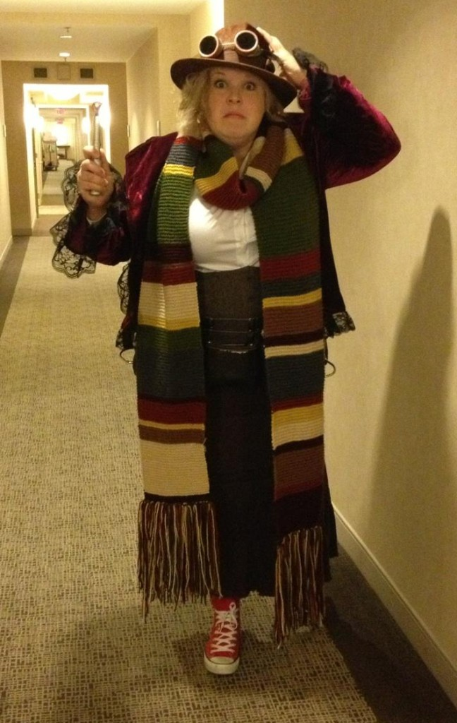 Me, dressed in a velvet frock coat, long 4th Doctor scarf, a tweed corset, hat and goggles, and red converse sneakers. I'm posing in a hotel hallway, with my best impression of Tom Baker's worried face.