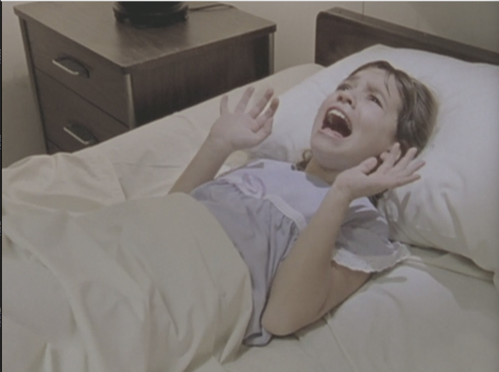 Celia in her hospital bed, screaming, with her hands up as though she's trying to push something away