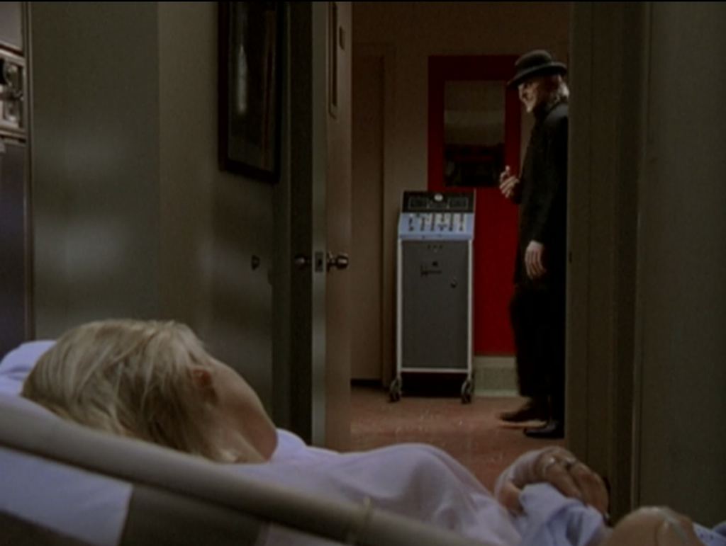 a man walking past Buffy's door. He's wearing all black with a black bowler hat, and has a cadaverous face with an eerie grin.