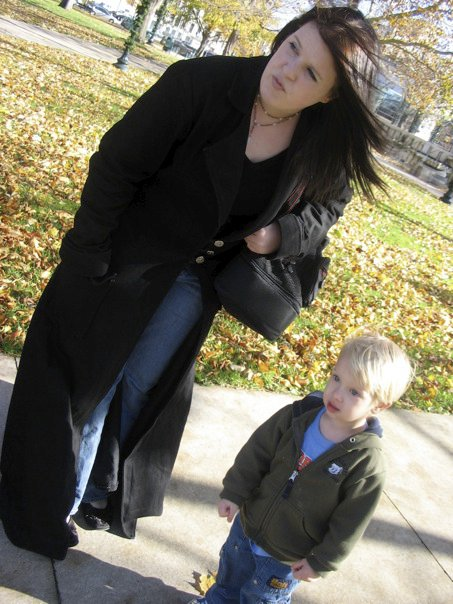Me with long black hair, long black coat, and a very small child.