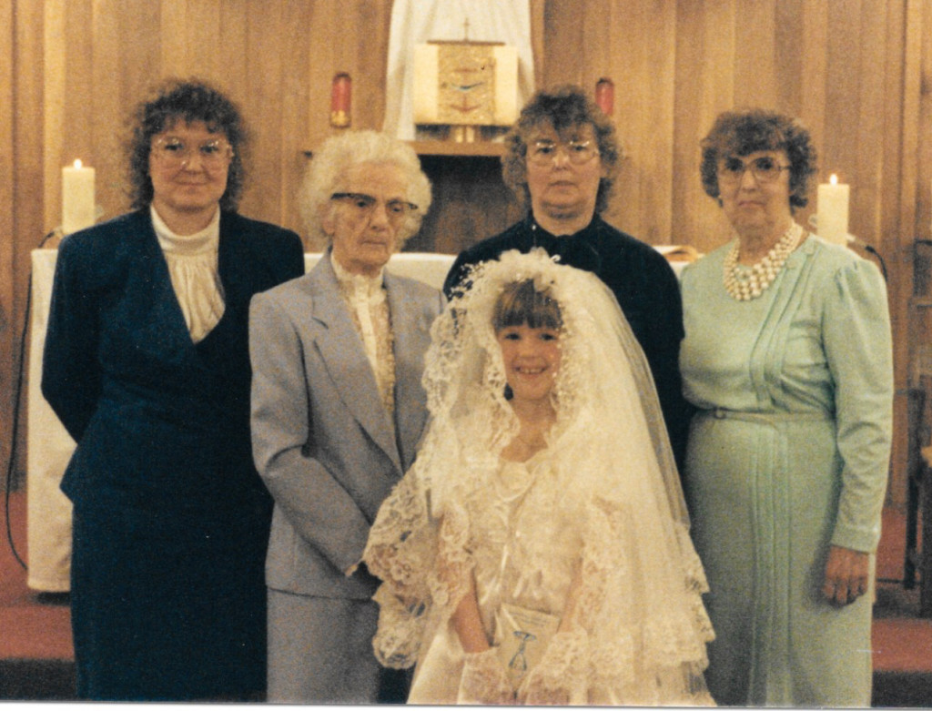 A photo of me, my mother, my grandmother, my great grandmother, and my great-great grandmother at my first communion.