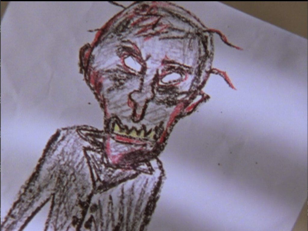 A crayon drawing of a creepy big-headed guy with lots of lower jaw teeth, a crooked nose, and white eyes.
