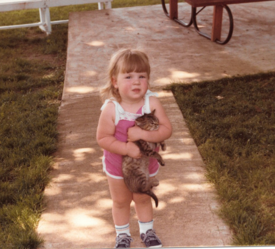 Me as a toddler, holding a cat by the neck.
