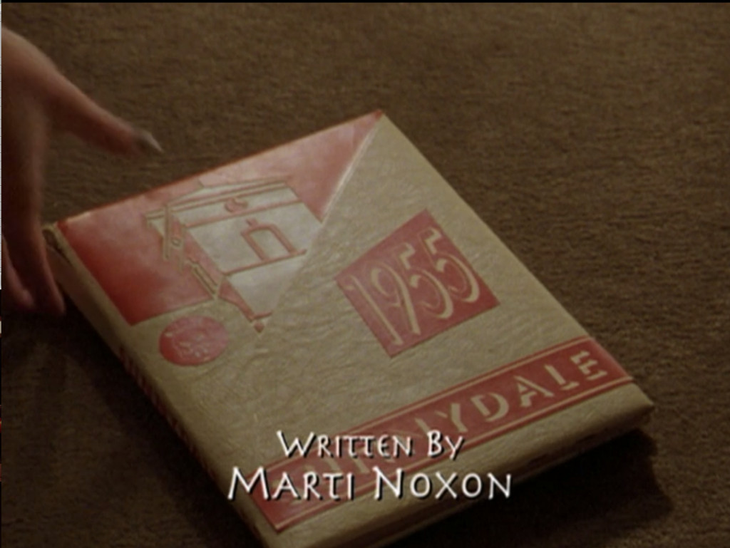 "Sunnydale yearbook from 1955. The credit title ""Written By Marti Noxon"" is displayed on the screen during this shot."