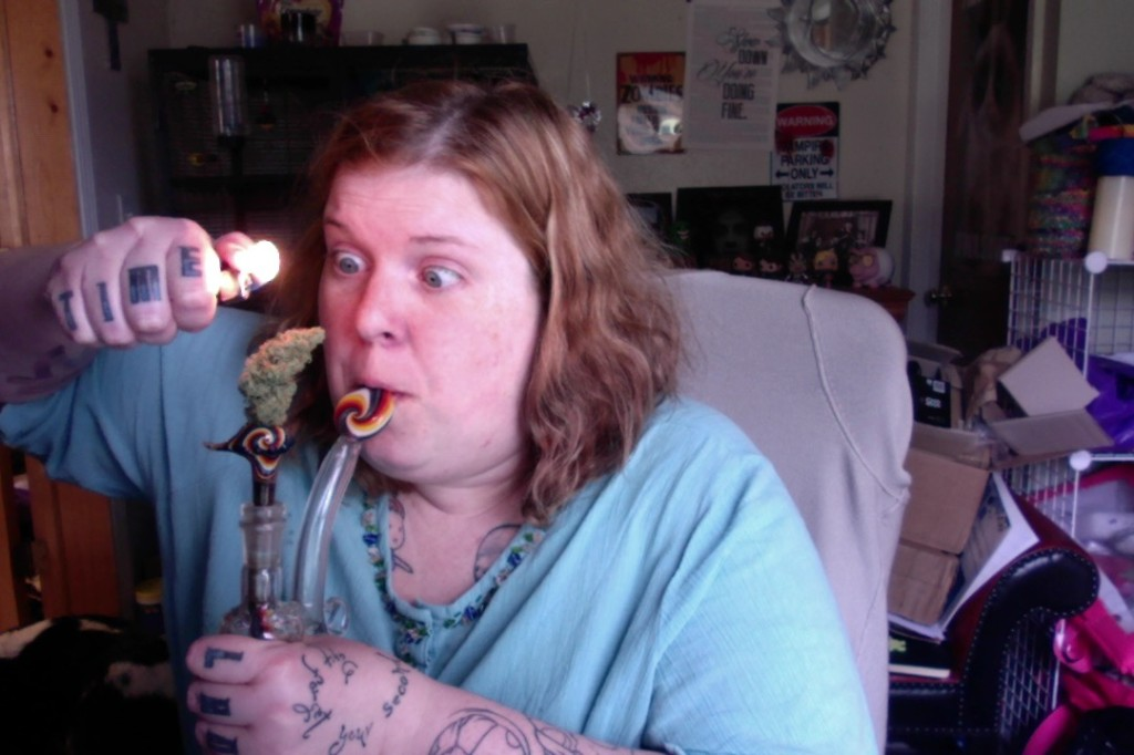 Me, pretending to take a hit off my bong, with a comically large bud (The size of a human ear) sticks out of the bowl.