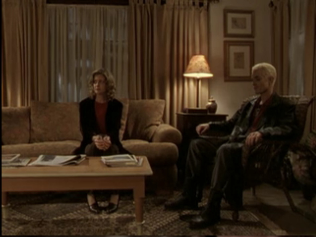Joyce sitting on the couch very primly, Spike sitting in a chair, neither of them speaking or looking at each other.