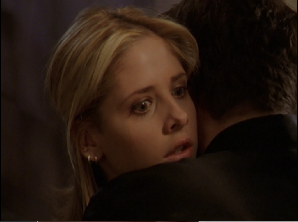 Buffy, looking over Angel's shoulder as the vortex opens.