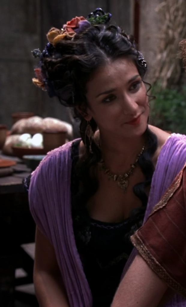 Actress Indira Varma, in purple robes, with her hair half up and little flowers and fruits and things stuck in it.