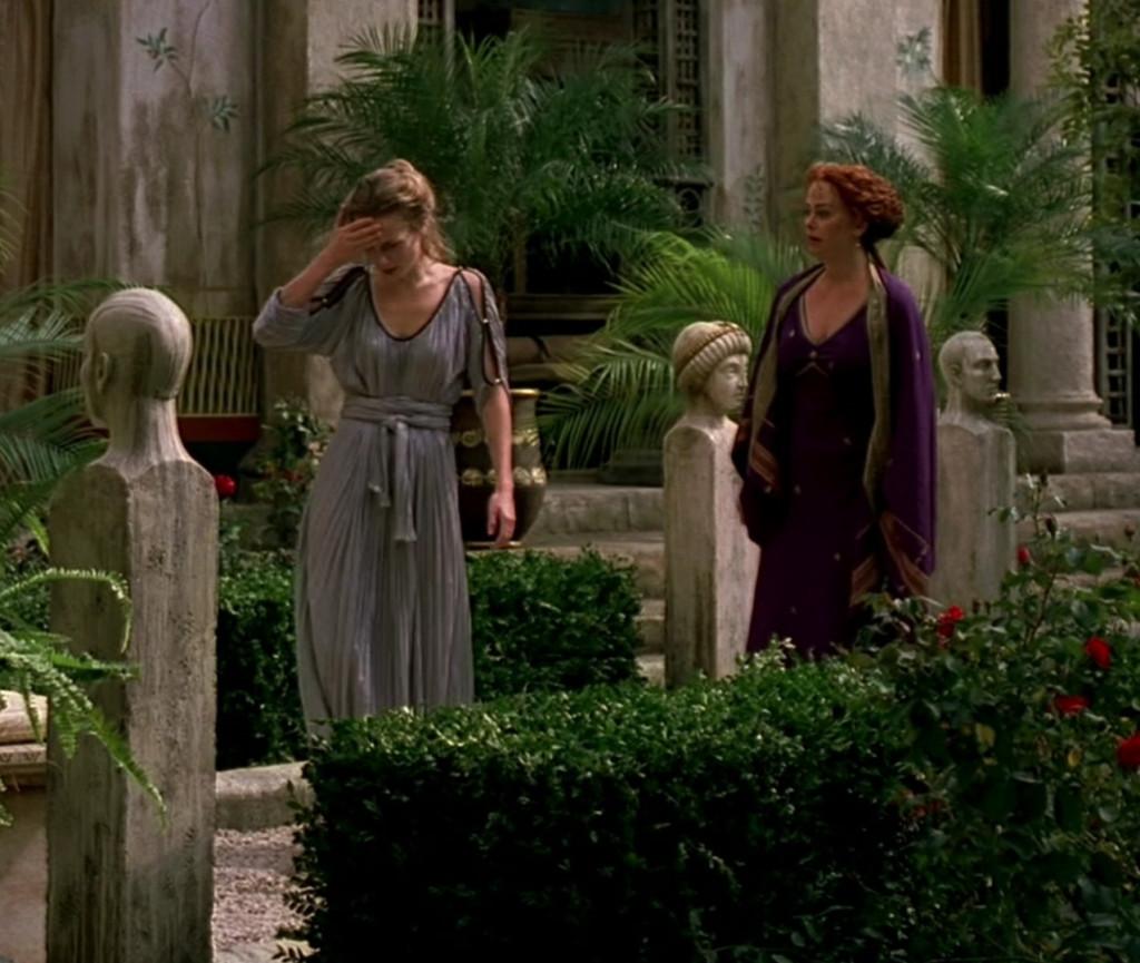 Octavia in a loose, flowing lavender dress, Atia in a tight, structured dark purple dress.