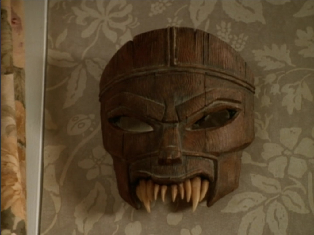 A wooden mask with angry eyes and sharp teeth