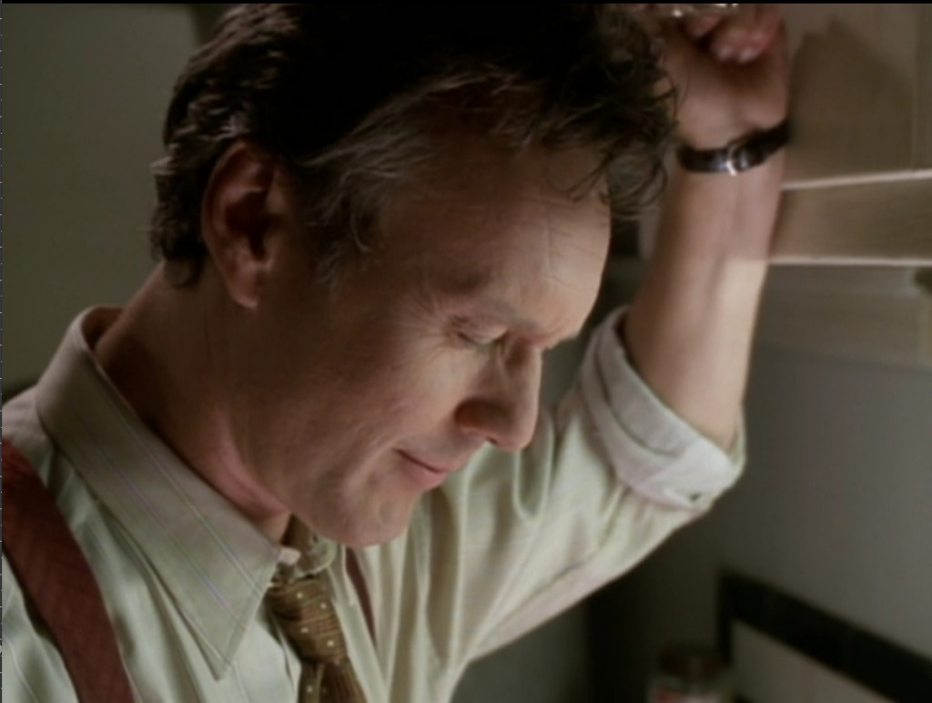 Giles leaning against a cupboard, his eyes closed, smiling.