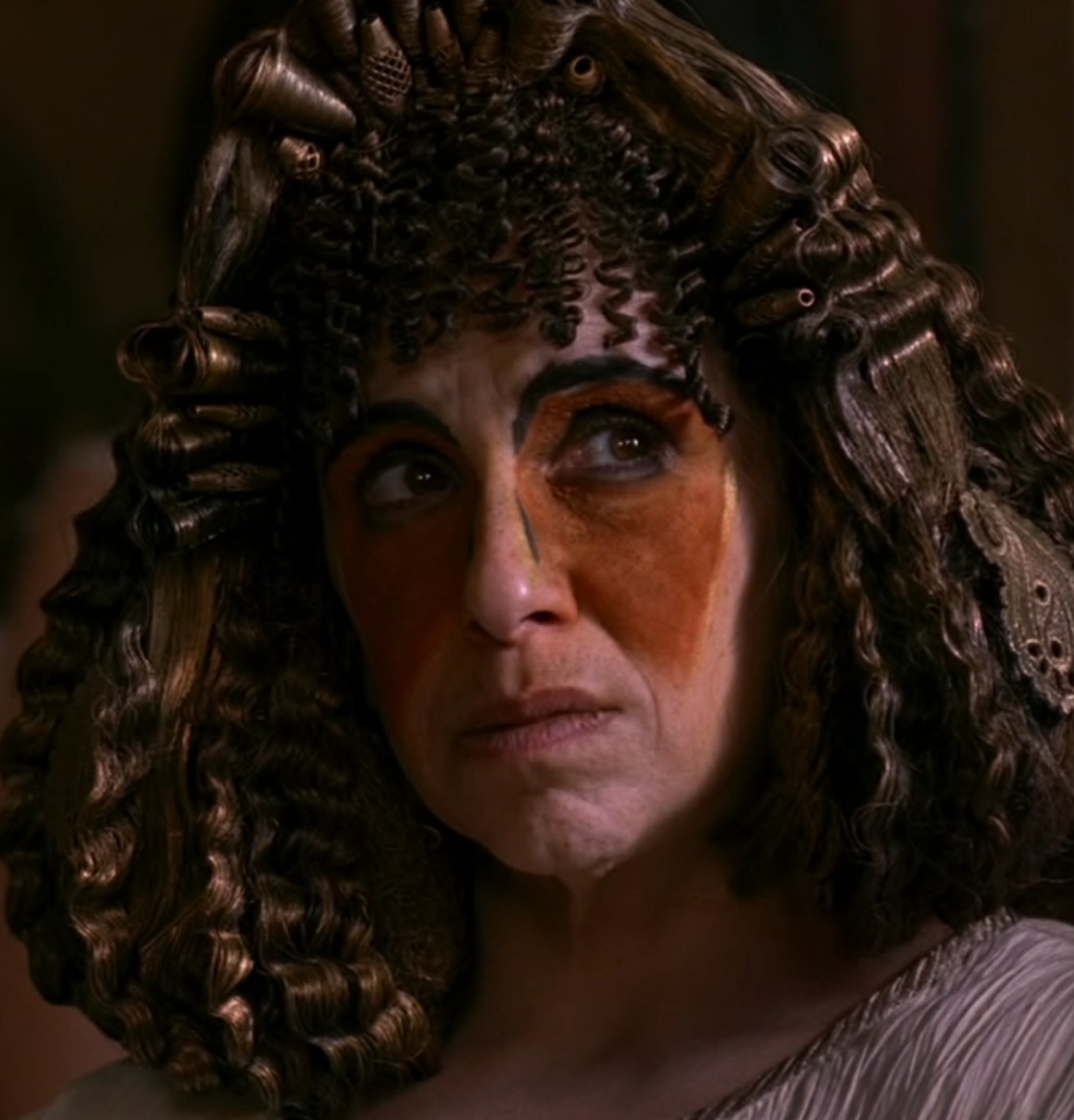 A middle-aged lady wearing a really busy wig with beads and starchy curls, with very exaggerated black eyebrows drawn on and triangles of rust-colored makeup over her eyes.