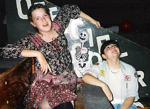 Me and my friend Jill on some bleachers, an inflatable skeleton between us. I'm wearing a vintage Gunne Sax dress, Jill is wearing a mechanic's shirt with patches. It was the '90s.