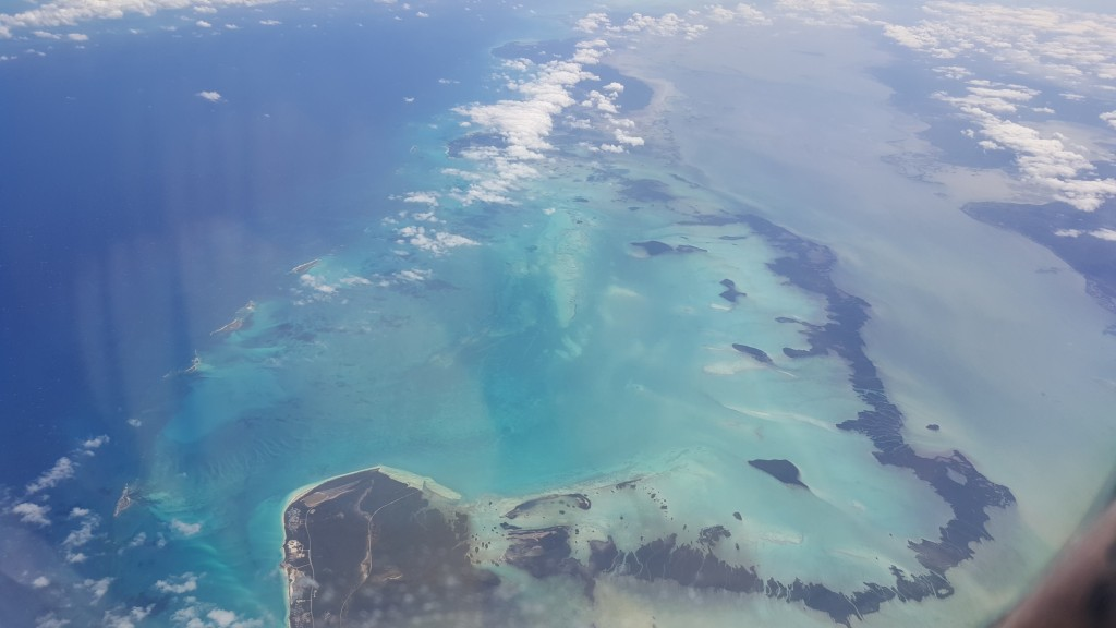 A view from the plane window of the sea and one of Cuba's little island chains.