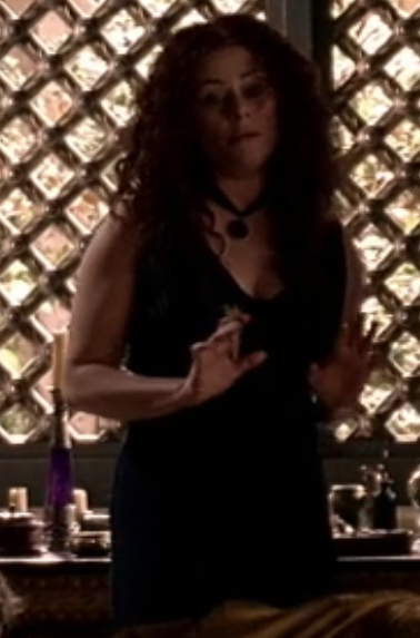 Atia has her hair down and center parted and curly, and she's wearing a black sheath dress and ribbon choker with a big round pendant.