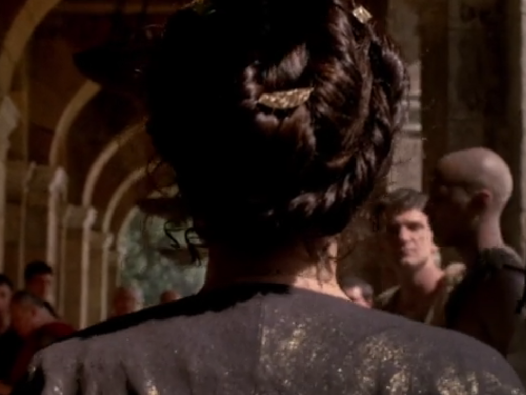 Cleopatra's hair is a configuration of  romantic-looking coils held with gold ornaments.