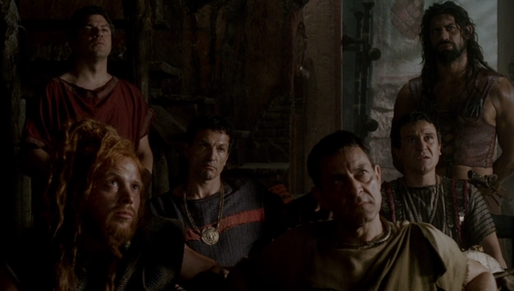In this group of several scary looking dudes in togas and leather armor and stuff, one guy is wearing a black toga with a red stripe across the chest, giving him the appearance of a guy wearing a track suit. He also has a big gold medallion on his necklace, and he's real, real Italian.