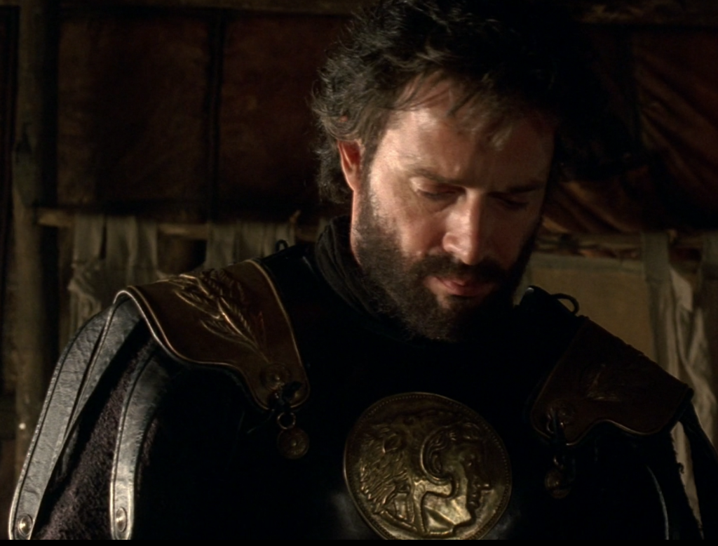 "There's really no good description for this beyond ""Antony has the same hairstyle and outfit as Alan Rickman in Robin Hood, Prince of Thieves,"" but I'll try. He has a black, sweptback mullet thing happening, as well as a beard, and all black armor."