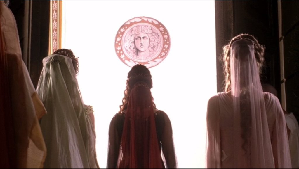 In front of an open door with blinding bright white light showing through a curtain with Octavian's picture on it, we see Atia from behind, standing in the center of and just slightly ahead of Livia and Octavia. It's really powerful, as Atia is framed by the doors and you get a sense that it's really her triumph, more than Octavian's.
