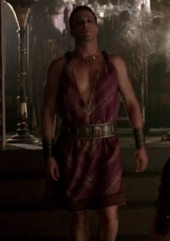 Antony is wearing a very short purple dress with a wide belt around it. The top is a super deep-v neck and sleeveless.