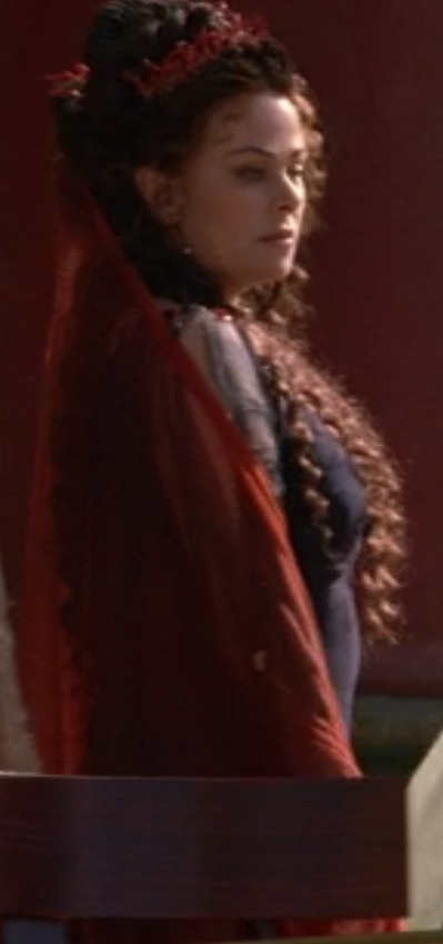 Atia's dress is really dark blue and tight and silky, with sheer sleeves. She's got a red scarf thing that's very gossamer and sheer, as well. Her hair is totally huge, like she's a Roman Marie Antoinette.