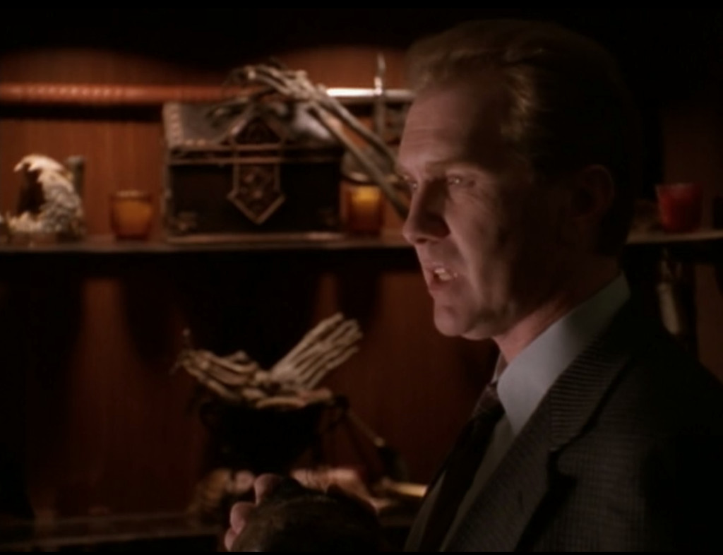 The Mayor is standing in front of a cabinet full of stuff like mysterious boxes and skeletal hands and shrunken heads.