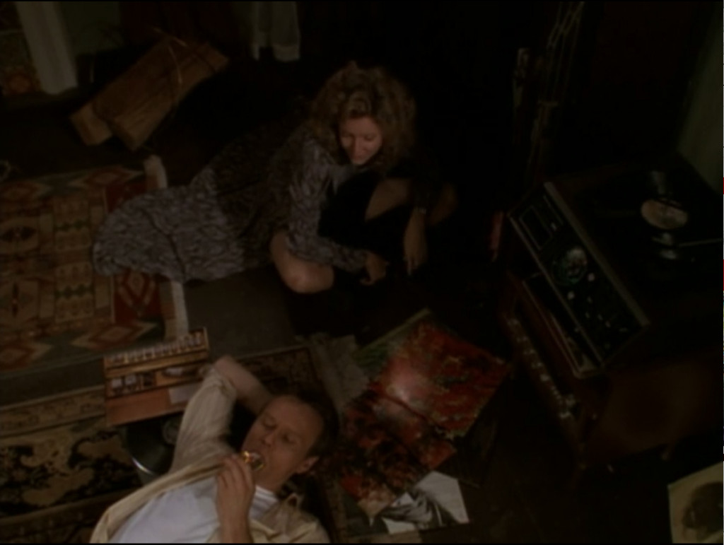 Giles is laying on the floor, lighting a cigarette. Joyce is sitting cross legged on the floor looking through record albums.