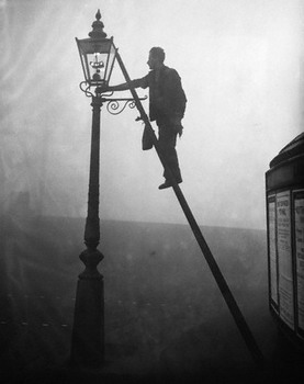A lamplighter on a ladder, lighting a gas street light.