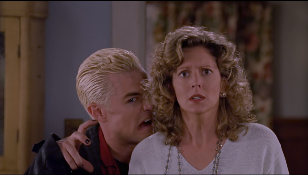 Spike stands behind Joyce, taunting Angel by making a goofy vampire face and a claw hand.