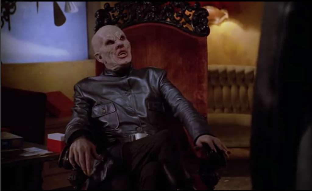 The leather clad, bald albino bat looking vampire from season one reclines sassily on a velvet throne.