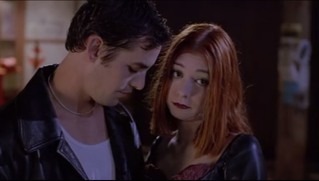 Willow and Xander are standing intimately close to each other. Xander is wearing a leather jacket a silver chain for some reason, and Willow has on dark makeup and a pleather corset get up.