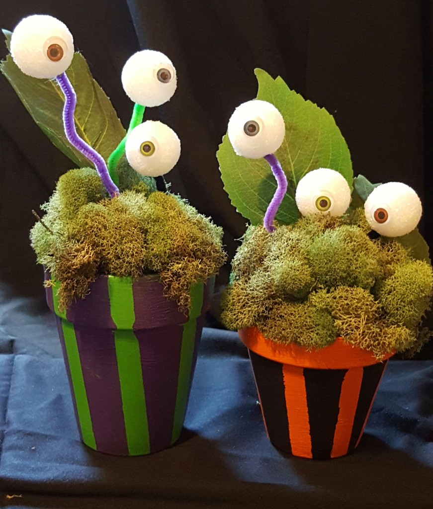 Two terracotta flower pots. One of them is painted with black and orange stripes. The other is painted with purple and green. Both of them contain mounds of moss and a fake leaf. Styrofoam balls with googly eyes on them are stuck on pipe cleaners that are stuck in the moss, giving the appearance of eyes growing on stalks like plants.