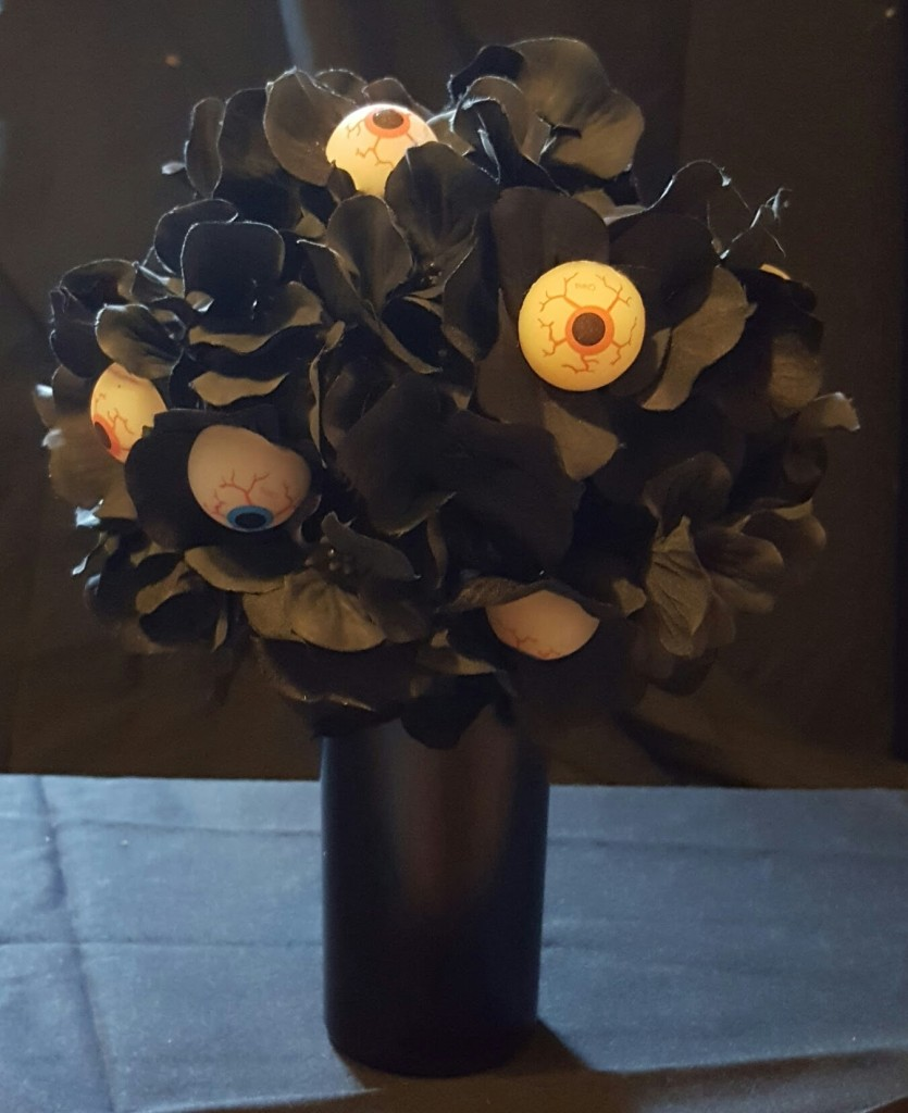 A black vase with black artificial flowers. Some of the flowers have eyeballs in them.