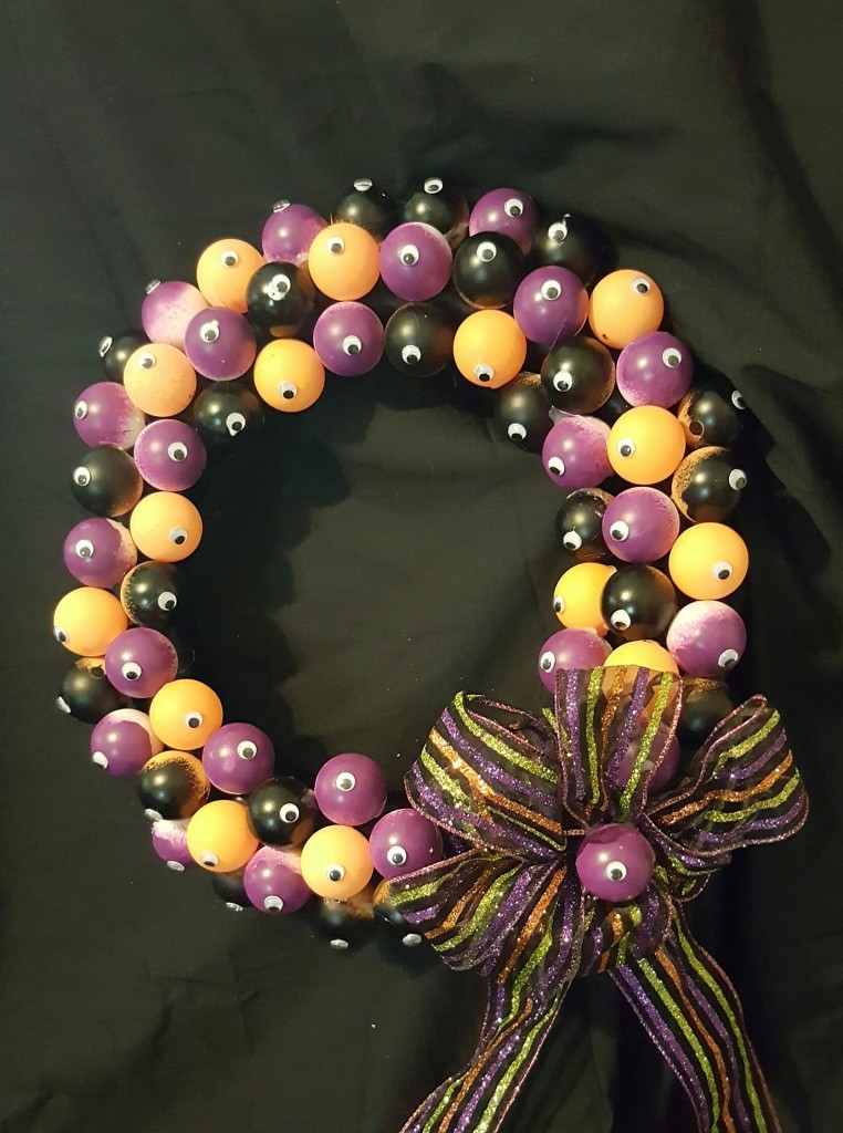 It's wreath covered in ping pong balls painted purple, black, and orange. Well, the orange ones aren't painted, they started out orange. Each ping pong ball has a single googly eye on it, and there's a big stripy bow in Halloween colors, with another little eyeball in the center.