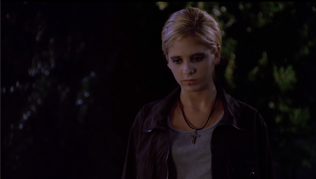 Buffy is wearing a grey shirt and a black leather jacket. Her hair is pulled back in a braid, she's got dark makeup on, and a big scar slashes across her lips.