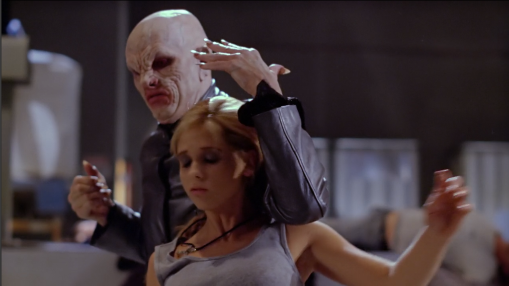 The Master is standing behind Buffy. His arm is on her shoulder, and he's just broken her neck, so she stares deadly off at nothing.