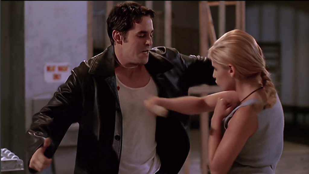 Buffy is driving a stake into Xander's chest.