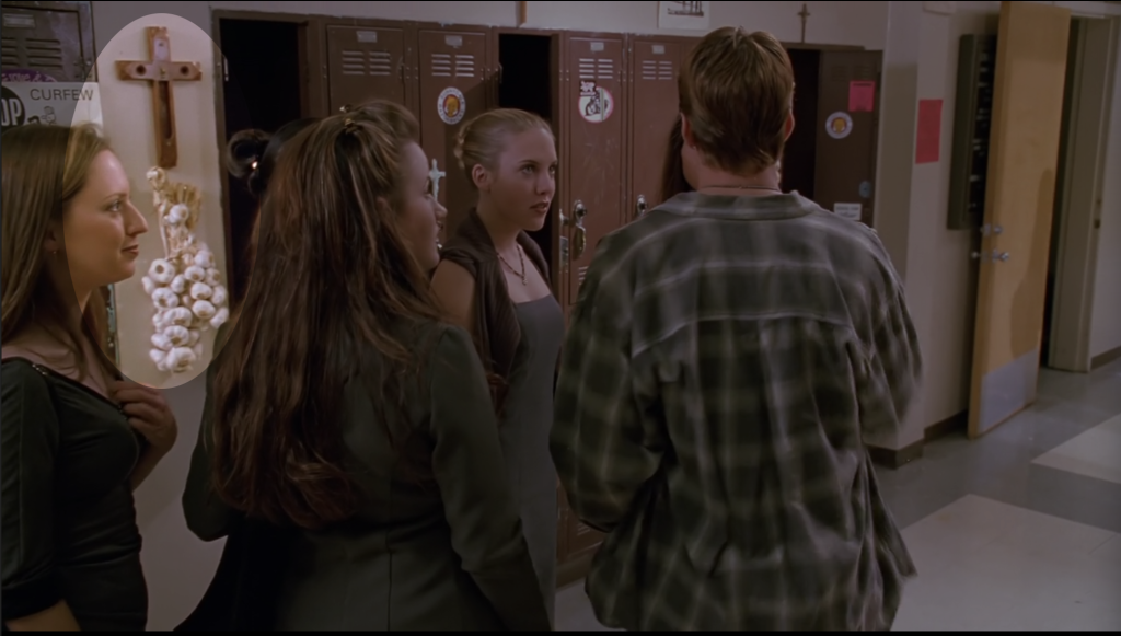 A shot of a Sunnydale High hallway. I've darkened most of the photo to highlight a small area, an oval around some garlic and a crucifix hanging between the lockers.