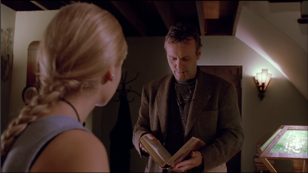 Now we're in Giles's apartment, looking over Buffy's shoulder (so it's a good shot of her Lara Croft braid) and Giles is wearing a tweed jacket now, but he still has the stubble and he's chewing on the end of one of the ear things of his glasses.