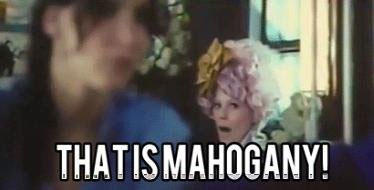 "Effie Trinket in The Hunger Games, with the text ""THAT IS MAHOGANY!"" over the bottom of the picture."