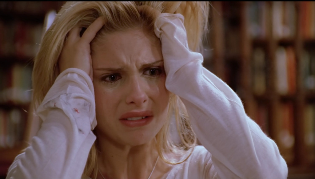 Buffy, crying, looking wounded, with her hands in her hair.
