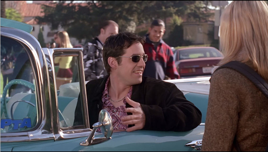 """Xander is not only driving this aqua-blue and white convertible with the top down on a day where other students are wearing coats, but he's also chosen some unfortunate sunglasses and a weird paisley shirt to go with his """"trying too hard"""" ensemble."""