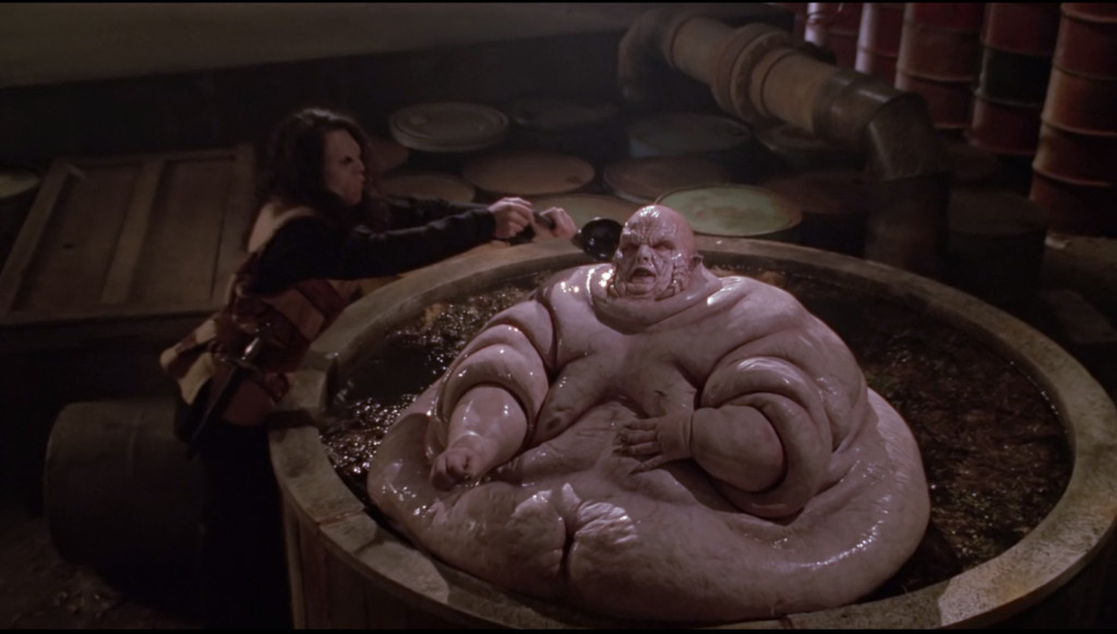 An enormously fat vampire, sitting naked in what appears to be chili. Another vampire is like, ladling liquid over him.