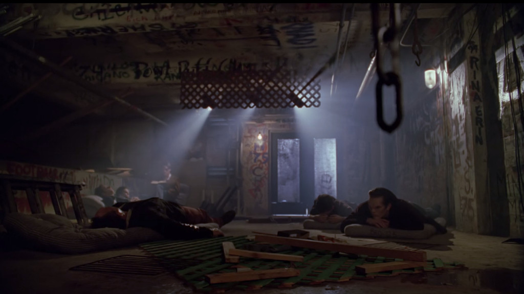 A bunch of vampires are sleeping on mattresses on the floor of a gross looking warehouse. One of them is reading in the corner.