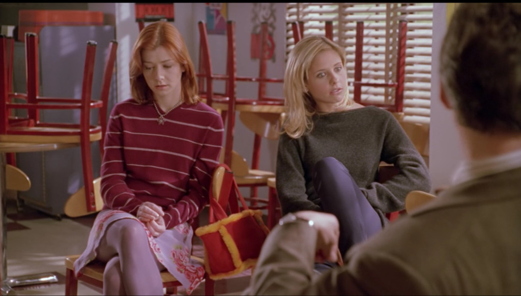 Same shot of Willow and Buffy sitting beside each other, only this time Buffy's facial expression makes it clear that she gets it now, too.