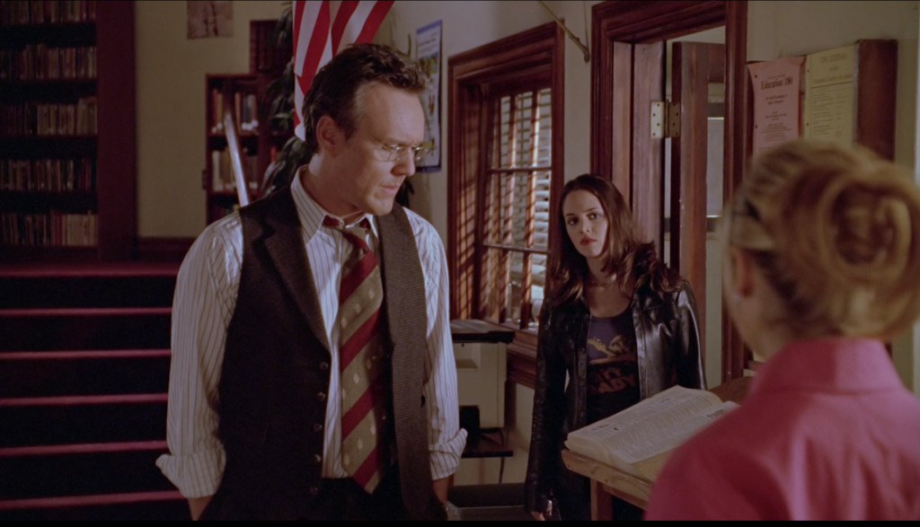 In the library, Giles stands with his back to Faith, who has just exited his office. Buffy stands in front of him (we see her from the back).