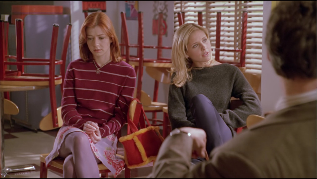 Willow sits next to Buffy. Buffy is still asking Xander questions, but we can tell from Willow's face that she gets it.
