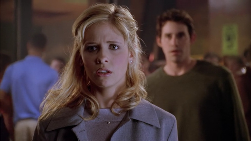Buffy is in the foreground, in focus. Xander is in the background, slightly out of focus. Both are shocked, but Buffy's expression is one of hurt, fear, and confusion. Also, her hair is half-up and super pretty, I don't know why they don't have her wearing it that way more often.