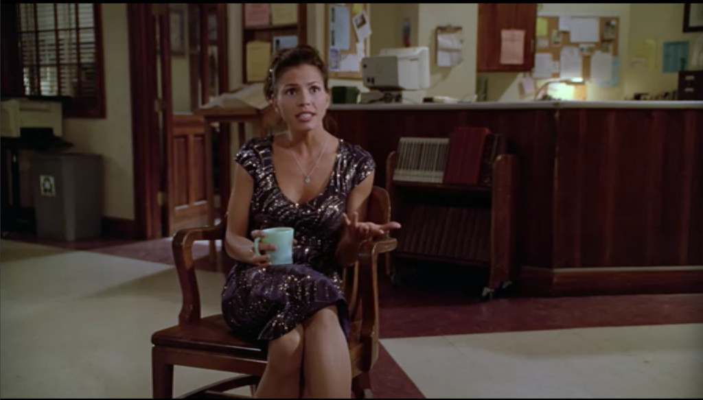 Cordelia is now seated, talking animatedly, gesturing with one hand while holding a mug in the other.