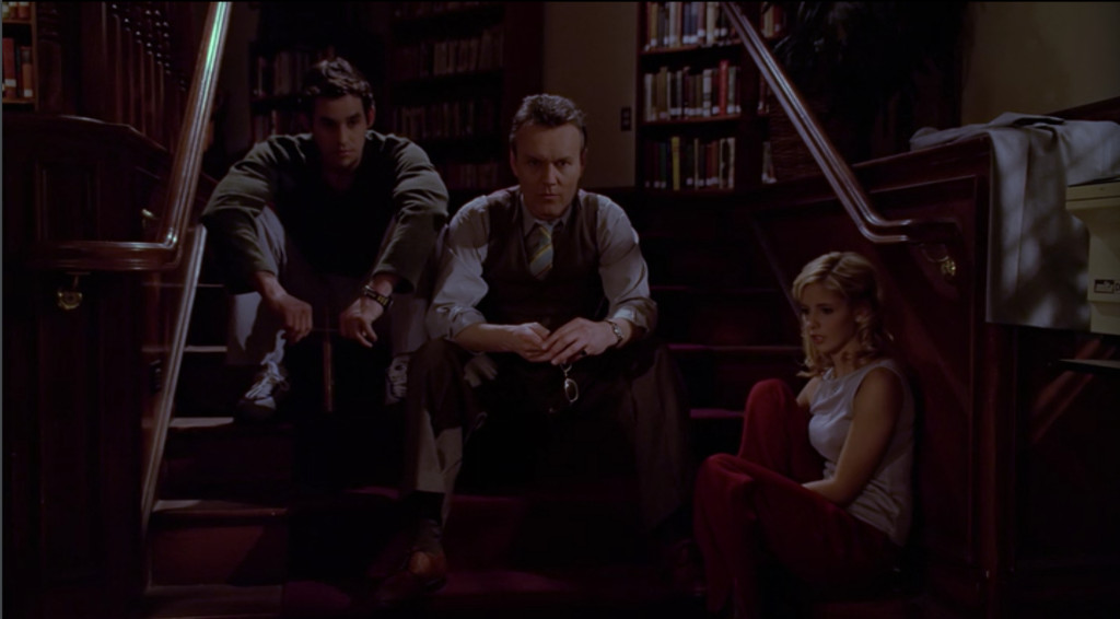 Buffy, Giles, and Xander sit on the steps in the library, in the dark, all with shocked/numb expressions.